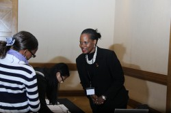Ms Adong Harriet, Communication Manager, RAN interacts with a participant arriving for the Launch