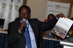Prof. William Bazeyo, Dean MakSPH-RAN CoP & Lab Director displaying the report at the discussion