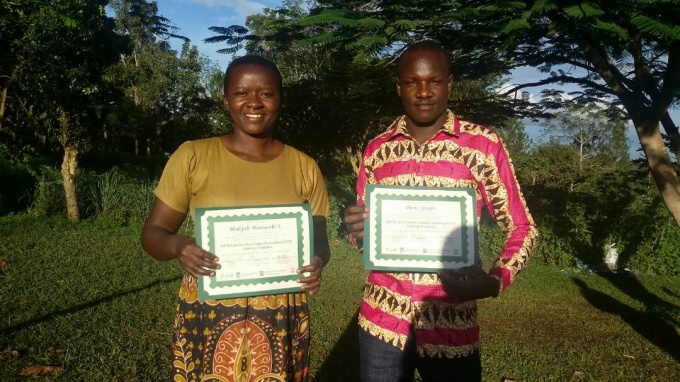 Hadijah Nantambi and Joseph Obore pose for a picture with their certificates as Creative Capacity Building Trainers of Trainees